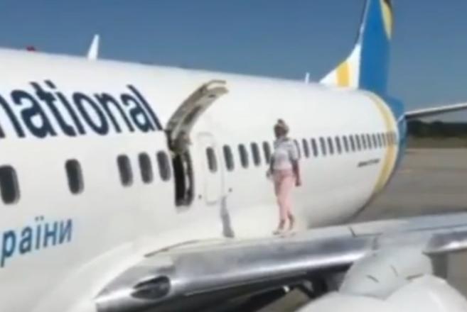 Пассажирка МАУ вышла подышать на крыло самолета через аварийный люк (видео)